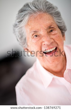 Portrait of a lovely old woman laughing - stock photo