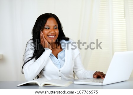 Portrait of a lovely relaxed student woman smiling and looking to a laptop at home indoor - stock photo