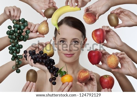 portrait of a lovely woman among lot of hands holding fruit - stock photo