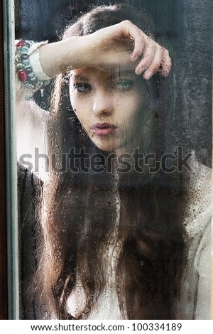 Portrait of a lovely young lady looking through glass window - Indoor in a dark cloudy day, she looks down at left,  her head is resting on the right arm and the left hand is near the chest - stock photo