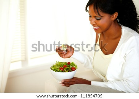Portrait of a lovely young woman smiling and looking to a vegetable salad. With copyspace. - stock photo