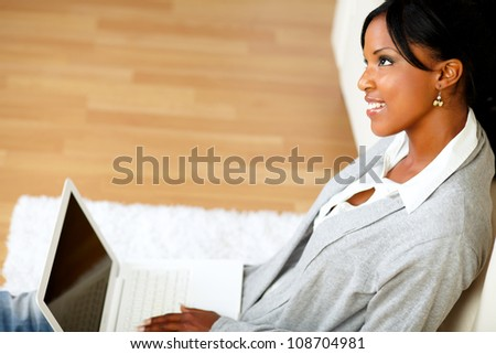 Portrait of a lovely young woman smiling and looking up while is sitting on the floor in front of her laptop - stock photo