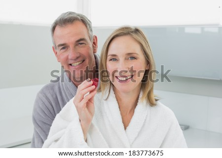 Portrait of a loving couple in bathrobes in the kitchen at home - stock photo