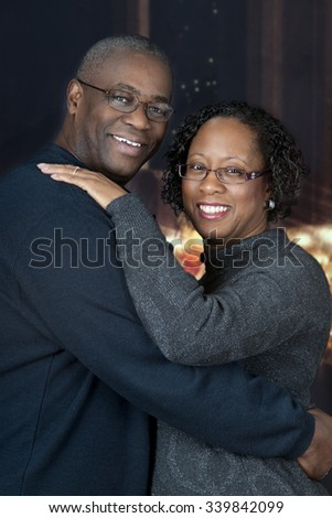 Portrait of a loving, mature, African AMerican couple with Christmas lights and a nighttime windows in the background. - stock photo