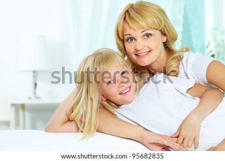 Portrait of a loving mother and her cute little daughter looking at camera with a smile