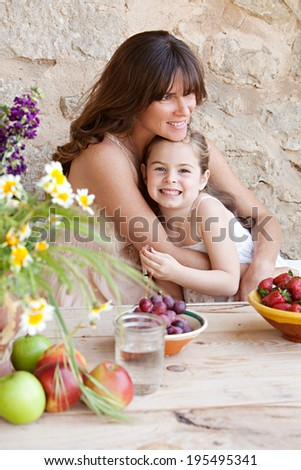Portrait of a loving mother and young daughter sitting together at a holiday home table outdoors eating fresh fruits and enjoying a summer vacation, hugging. Family fun and healthy eating. - stock photo