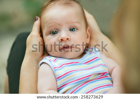 Portrait of a loving mother holding her cute baby with gorgeous blue eyes on his back, in her lap in the garden - stock photo