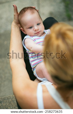 Portrait of a loving mother looking at her beautiful baby with gorgeous blue eyes on his back, in her lap in the garden looking at each other - stock photo