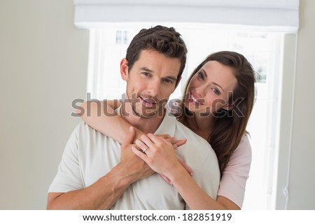 Portrait of a loving young woman embracing man from behind at home - stock photo