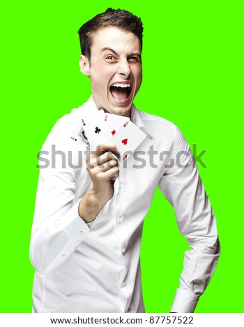 portrait of a lucky young man showing poker cards over a removable chroma key background - stock photo