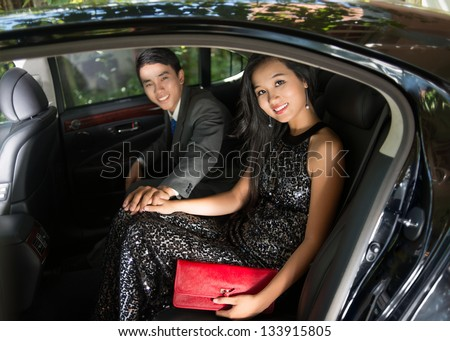 Portrait of a luxury young couple sitting in a car - stock photo