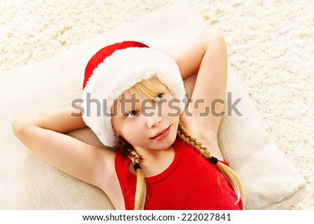 portrait of a lying girl in a Santa hat. Christmas child - stock photo