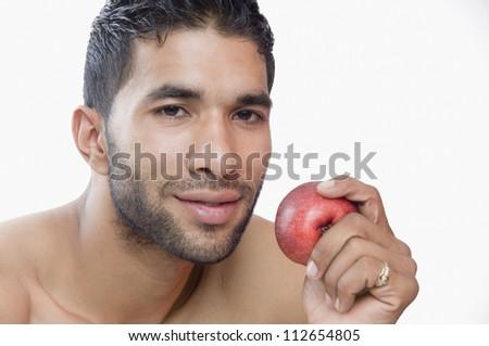 Portrait of a macho man eating apple - stock photo