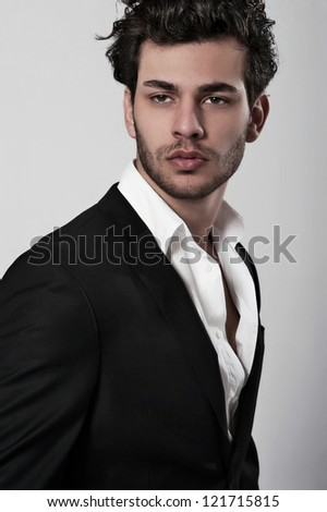 Portrait of a macho man holding jacket against grey background - stock photo
