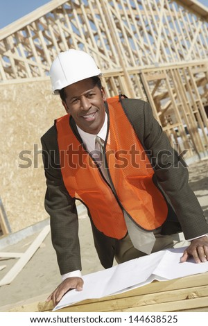 Portrait of a male African American surveyor with blueprints at construction site - stock photo