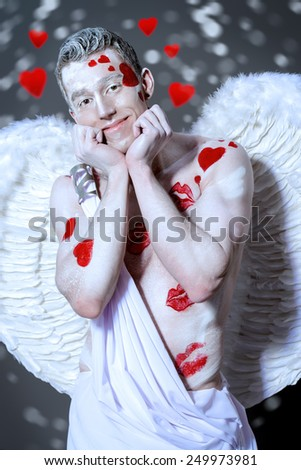 Portrait of a male Angel Cupid smiling at camera. Valentine's day. Love concept. - stock photo