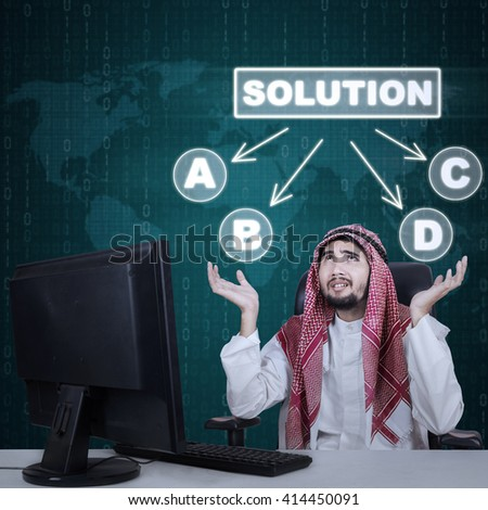 Portrait of a male Arabian worker working in the office and looks confused to choose a solution - stock photo
