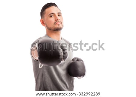 Portrait of a male boxer challenging the camera to a match on a white background - stock photo
