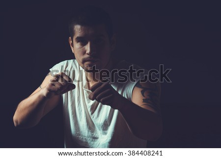 Portrait of a male boxer. Young sporty man on a dark background. Toned image. Fight