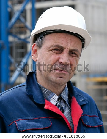 Portrait of a male builder, engineer on the background of a construction site. The white helmet, overalls. Wrinkles, tired, experienced look