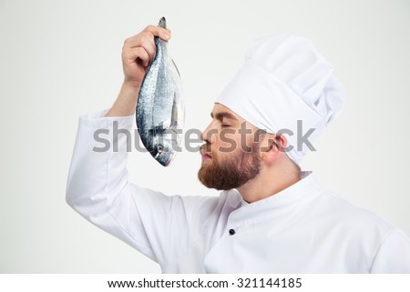 Portrait of a male chef cook smelling fresh fish isolated on a white background