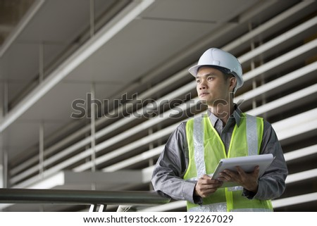 Portrait of a male Chinese industrial engineer at work - stock photo