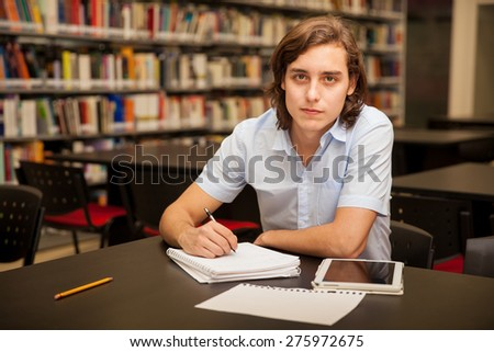 Portrait of a male college student taking some notes and using a tablet computer in the library - stock photo