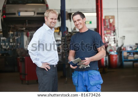 Portrait of a male customer standing with mechanic outside the garage - stock photo