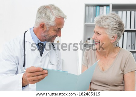 Portrait of a male doctor and senior patient with reports at medical office - stock photo