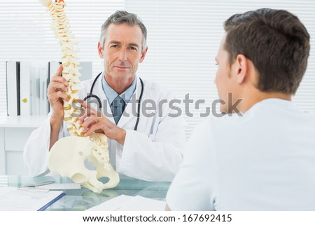 Portrait of a male doctor explaining the spine to a patient in medical office