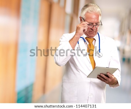 Portrait Of A Male Doctor Holding A Tab, Indoor - stock photo