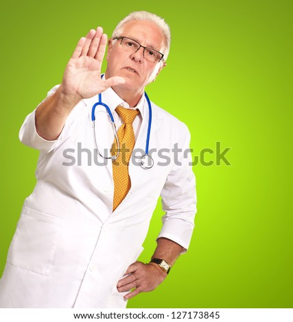 Portrait Of A Male Doctor Showing Warning Sign On Green Background - stock photo