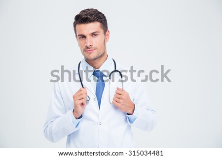 Portrait of a male doctor standing with stethoscope isolated on a white background - stock photo