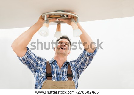 Portrait Of A Male Electrician Fixing Light On Ceiling - stock photo