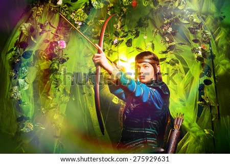 Portrait of a male elf with a bow and arrows in a magical forest. - stock photo