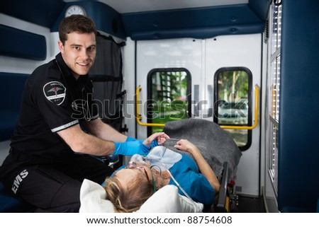 Portrait of a male EMT inside ambulance with senior woman patient - stock photo