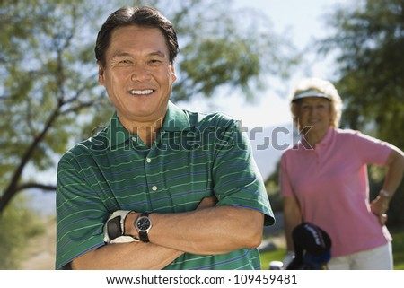 Portrait of a male golfer with woman standing in background