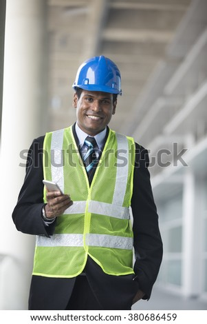 Portrait of a male Indian, industrial engineer at work. Asian engineer smiling & looking at the camera. - stock photo