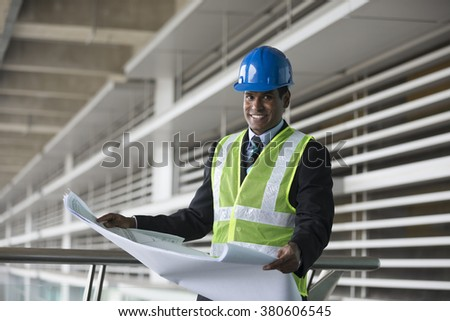 Portrait of a male Indian industrial engineer at work holding technical drawing plans. Looking at the camera.