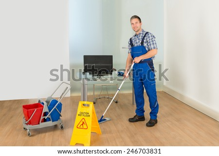 Portrait Of A Male Janitor Cleaning Office With Mop And Wet Floor Sign - stock photo