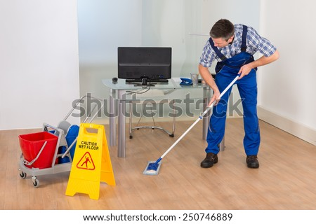 Portrait Of A Male Janitor Cleaning Office With Wet Floor Sign - stock photo