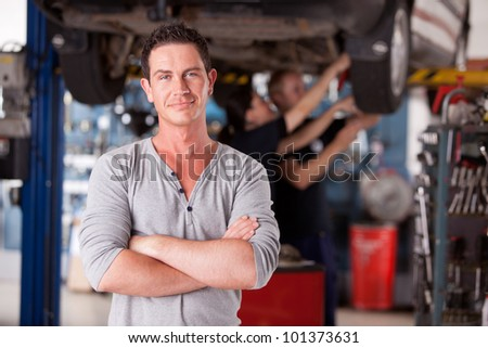 Portrait of a male mechanic looking at the camera with workers in the background - stock photo