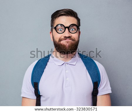 Portrait of a male nerd with funny face over gray background - stock photo