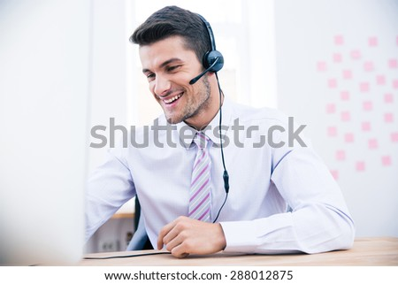 Portrait of a male operator with headset using PC in office - stock photo