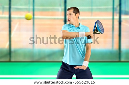 portrait of a male paddle tennis player with racket ready to hit the ball at sports facilities