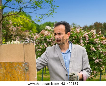 Portrait of a male painter wearing a glove in the process outdoors painting his masterpiece - stock photo