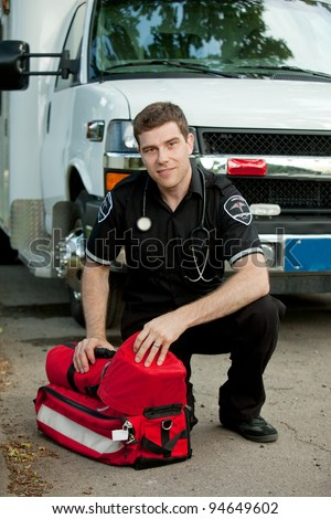 Portrait of a male paramedic in front of ambulance with portable oxygen unit - stock photo