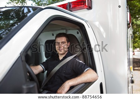 Portrait of a male paramedic sitting in driver seat of white ambulance - stock photo