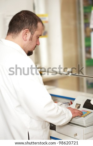 Portrait of a male pharmacist at pharmacy. Selling - stock photo