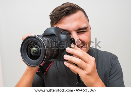 Portrait of a male photographer with camera taking photo isolated on a gray background